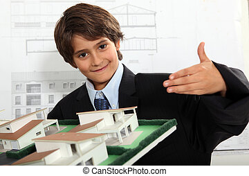 Boy dressed as a businessman in an architects office