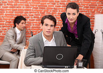 Young co-workers watching laptop
