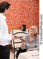 mature lady being served by waiter at restaurant