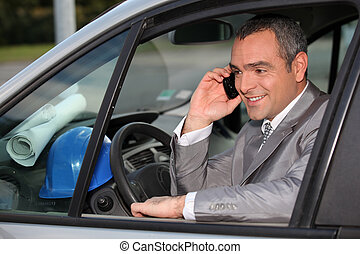 Architect in car using mobile telephone