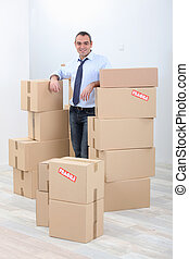 Man with piles of cardboard boxes marked fragile