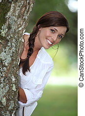 Smiling woman leaning out from behind a tree