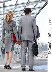 Business couple arriving at airport