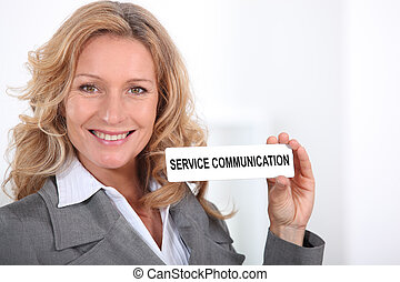 "Woman in a suit holding a ""Service Communication"" sign"