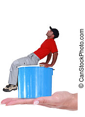 Worker with cap sat on paint can