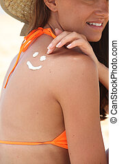 a woman drawing a face on her back with suntan lotion