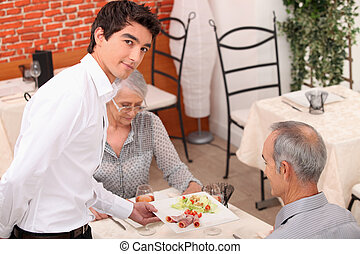 Young waiter serving senior couple in restaurant