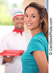 Delivery man bringing pizzas to young woman