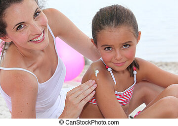 A woman putting suncream on her daughter.