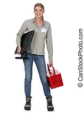 blonde woman holding a computer screen and a tool box