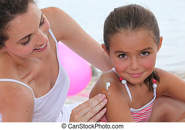 Mother putting suncream on her daughter