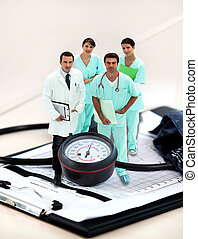 portrait of medical staff  amid giant clipboard and sphygmomanometer