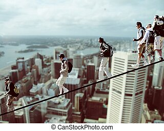 Climbers on a rope with cityscape in the background,...