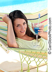 Woman having a cocktail drink in a hammock