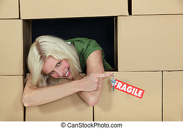 woman surrounded by parcels holding a key and smiling