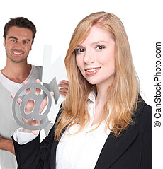 Office couple stood with at symbol