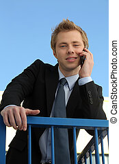 Young businessman speaking on his mobile phone outdoors