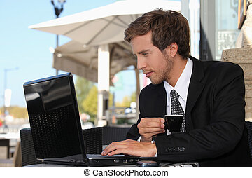 business man drinking coffee and watching his laptop on a...