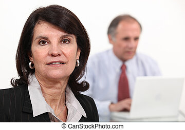 Mature businesswoman and man using a laptop