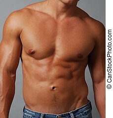 Shirtless muscular male chest and abdomen - closeup of a...
