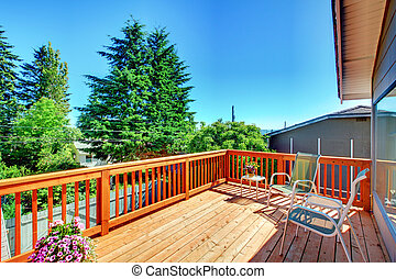 Large new wood deck home exterior with chairs. - Large new...