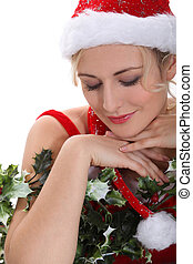 blonde woman wearing a Christmas costume hugging holly and...