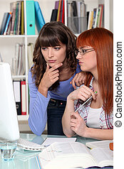Two confused girls looking at computer screen