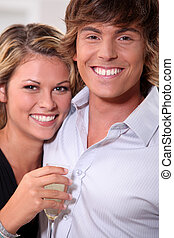 young couple with toothy smile and flute of wine
