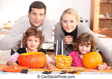 A family carving Halloween pumpkins.