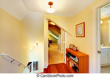 Yellow low ceiling home hallway with staircase interior. -...