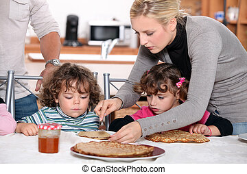 Parents preparing breakfast for children