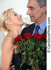 Couple embracing with a bunch of roses
