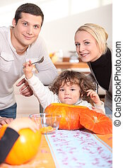 a little child  eating a pumpkin and his parents