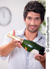 A man offering a bottle of champagne.