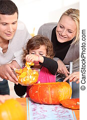 Young family carving Halloween pumpkins