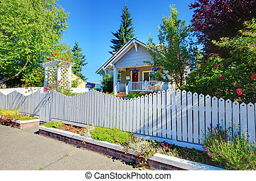Cute old grey house behind white fence. - Charming old cute...