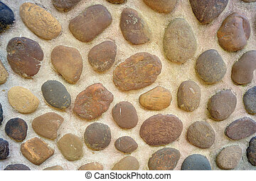 Abstract pebbles round textured wall.