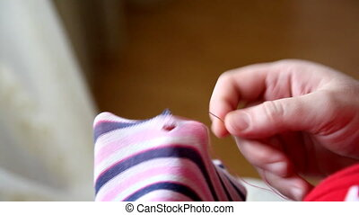 needle - A woman sews up the hole with a needle