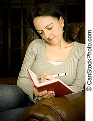 woman writing in diary - woman sitting in armchair writing...