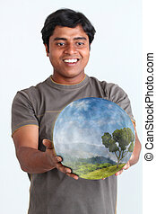 Person holding glowing ball containing ecosystem - Person...