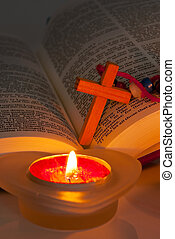 Open Bible with cross and burning candles. Bible text is...