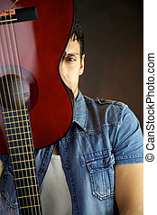 Male model hiding behind guitar