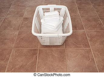 Clean white towels in a laundry basket