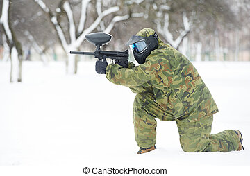 paintball player with marker at winter outdoors - paintball...