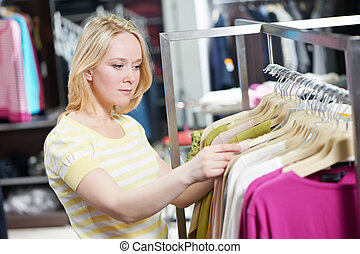 Young woman at clothes shopping store - Young woman choosing...