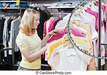 Young adult woman at clothes shopping - Young woman choosing...