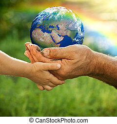 Earth - Senior man and baby holding the Earth in hands...