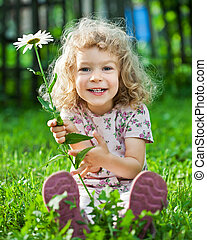 Child with flower - Happy smiling child with flower sitting...