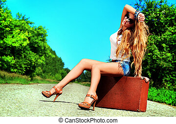 waiting for car - Pretty young woman hitchhiking along a...