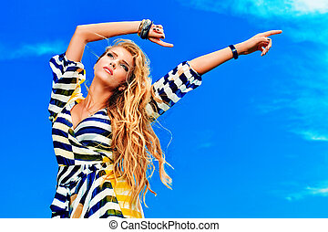 romantic sky - Beautiful young woman outdoors over blue sky.